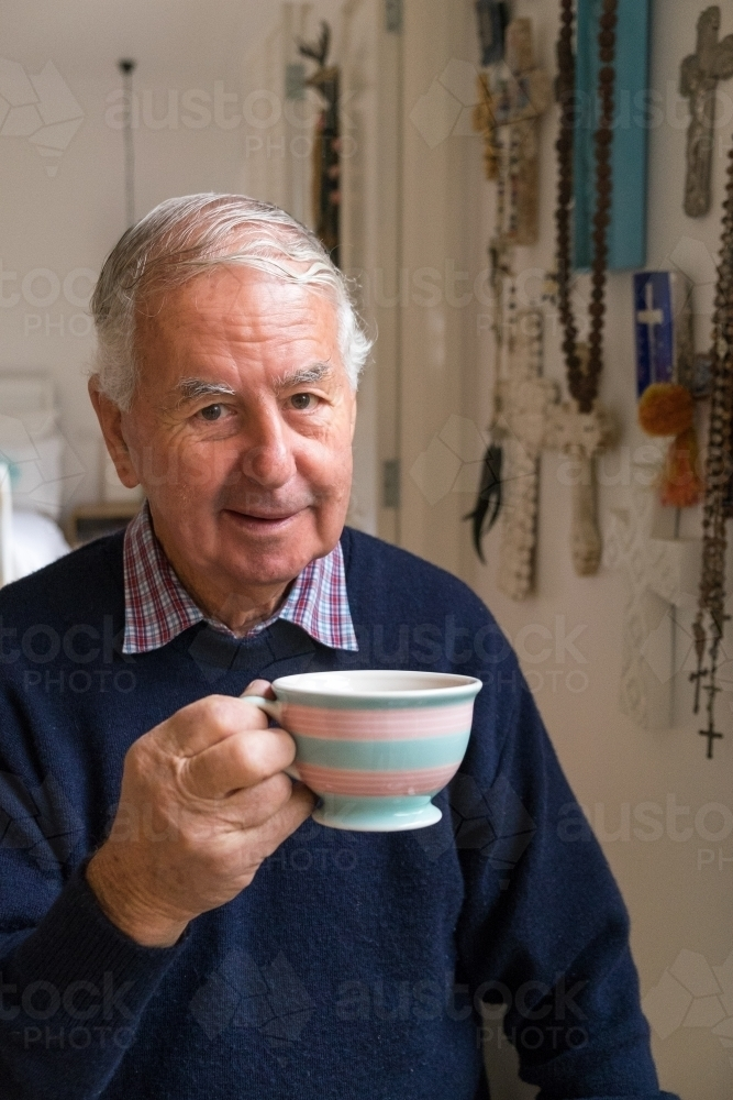 Old man with a cup of tea looks at the camera - Australian Stock Image