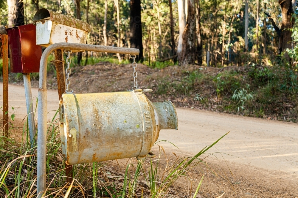 Old milk can as country mailbox at property entrance - Australian Stock Image