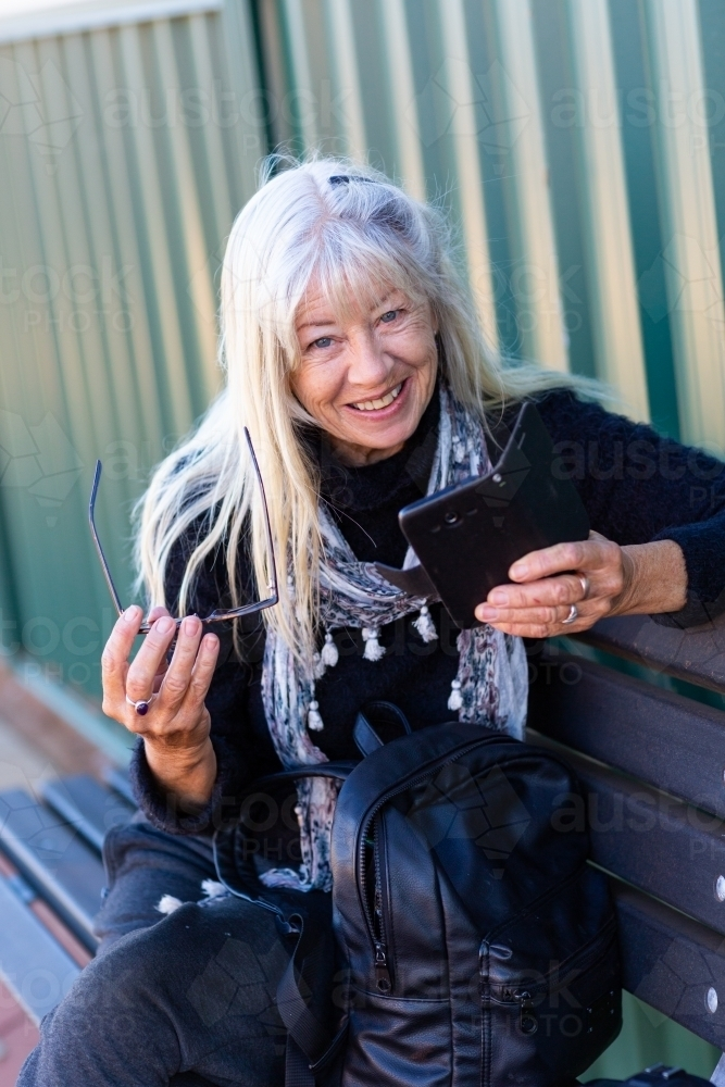 Older lady holding mobile phone and smiling - Australian Stock Image