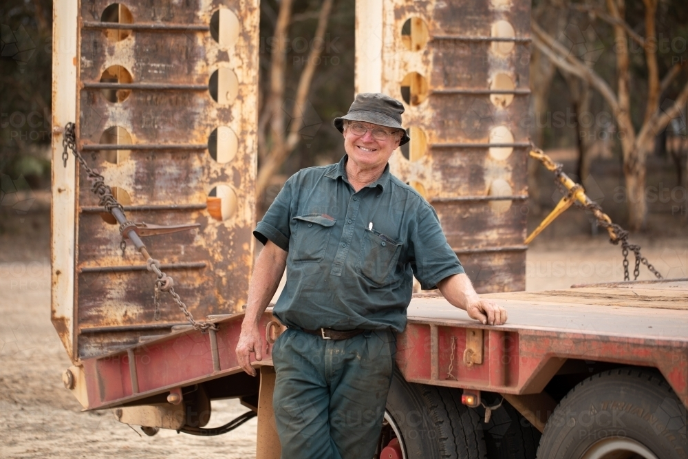 older man smiling and leaning on truck tray - Australian Stock Image