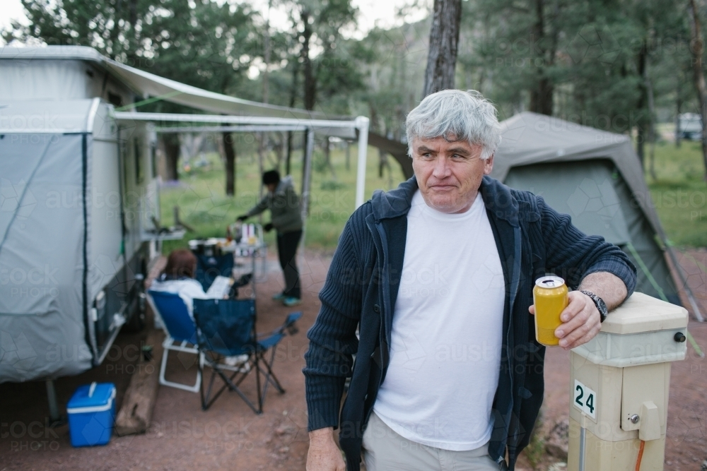 Older man standing in front of a caravan and tent with a beer - Australian Stock Image