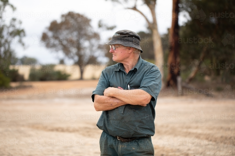 older man with grim look on his face and arms folded looking away - Australian Stock Image