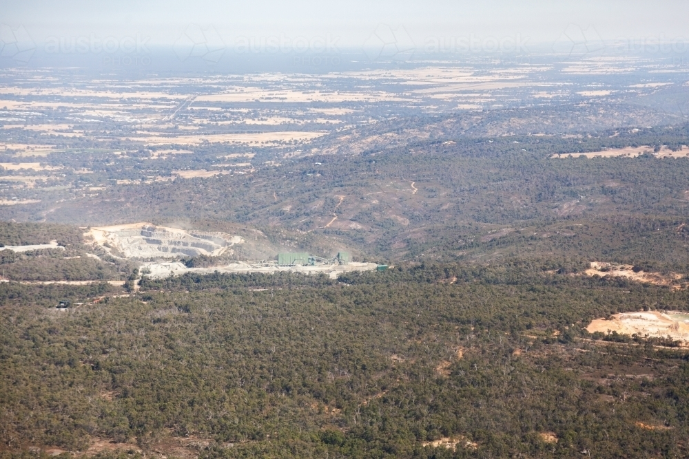 Open cut mine or quarry seen from the air among trees - Australian Stock Image