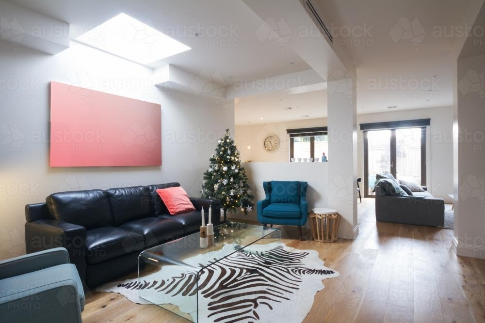 Open plan casual living room in contemporary home with christmas tree - Australian Stock Image