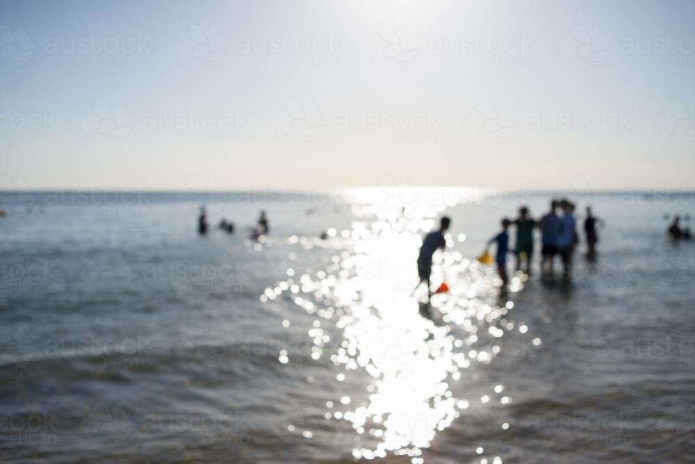 Out of focus view of people at the beach standing in the water - Australian Stock Image