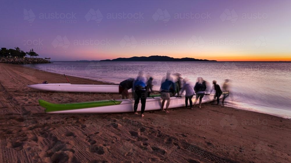Outrigger canoe team preparing for a dawn training paddle. - Australian Stock Image