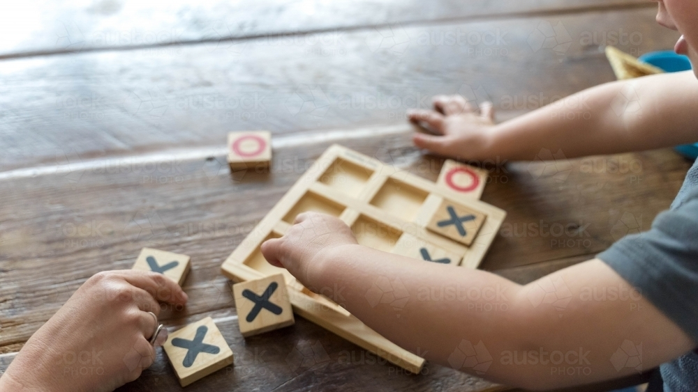 Over the shoulder shot of childs hands doing puzzle - Australian Stock Image
