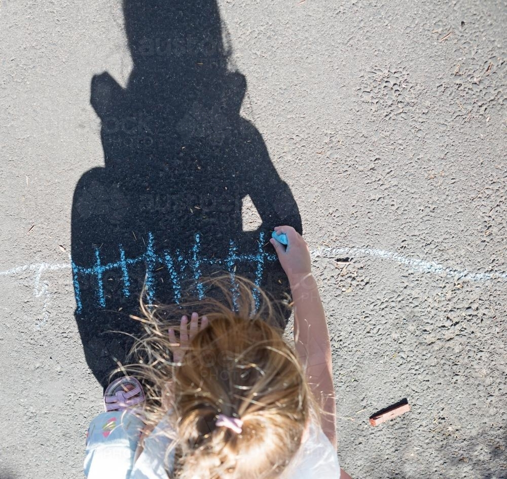 Overhead shadow of a young girl drawing with chalk on the road - Australian Stock Image