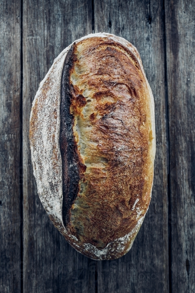 Overhead shot of organic white sourdough on wooden bench - Australian Stock Image