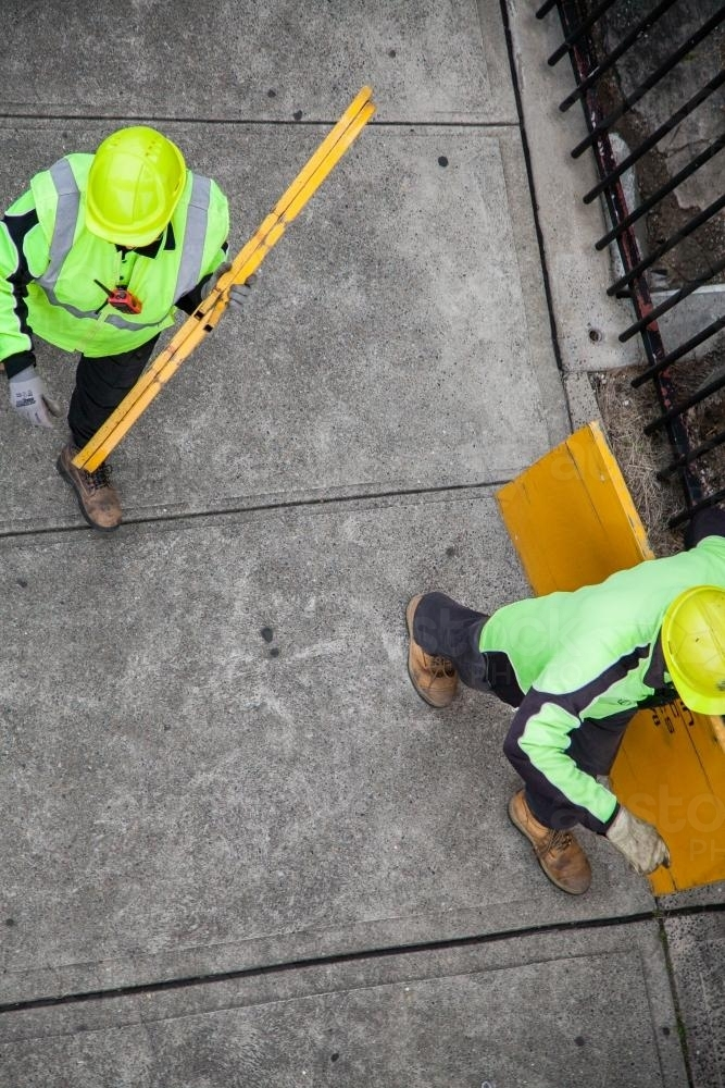 Overhead view of two workers in yellow carrying road signs - Australian Stock Image