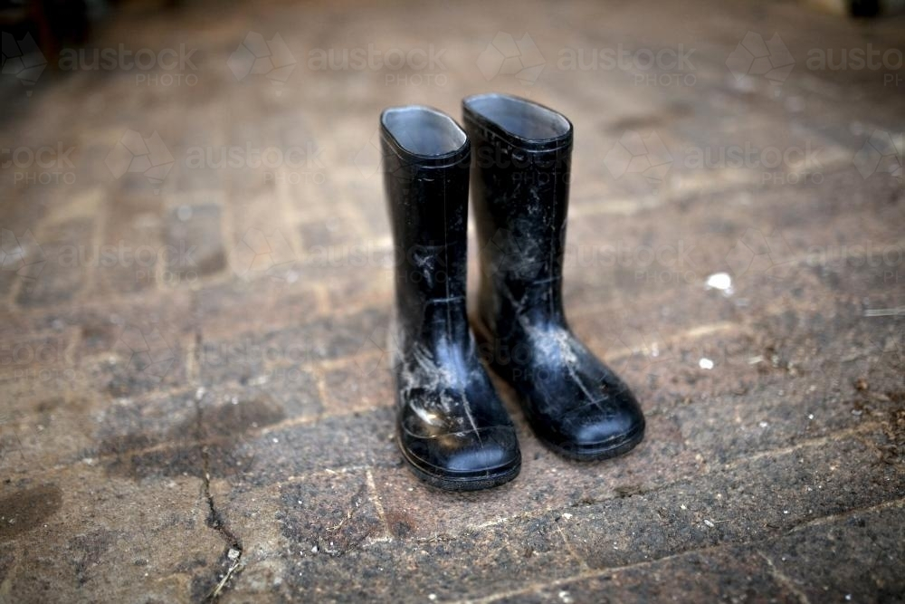 Pair of black gumboots on paved ground - Australian Stock Image