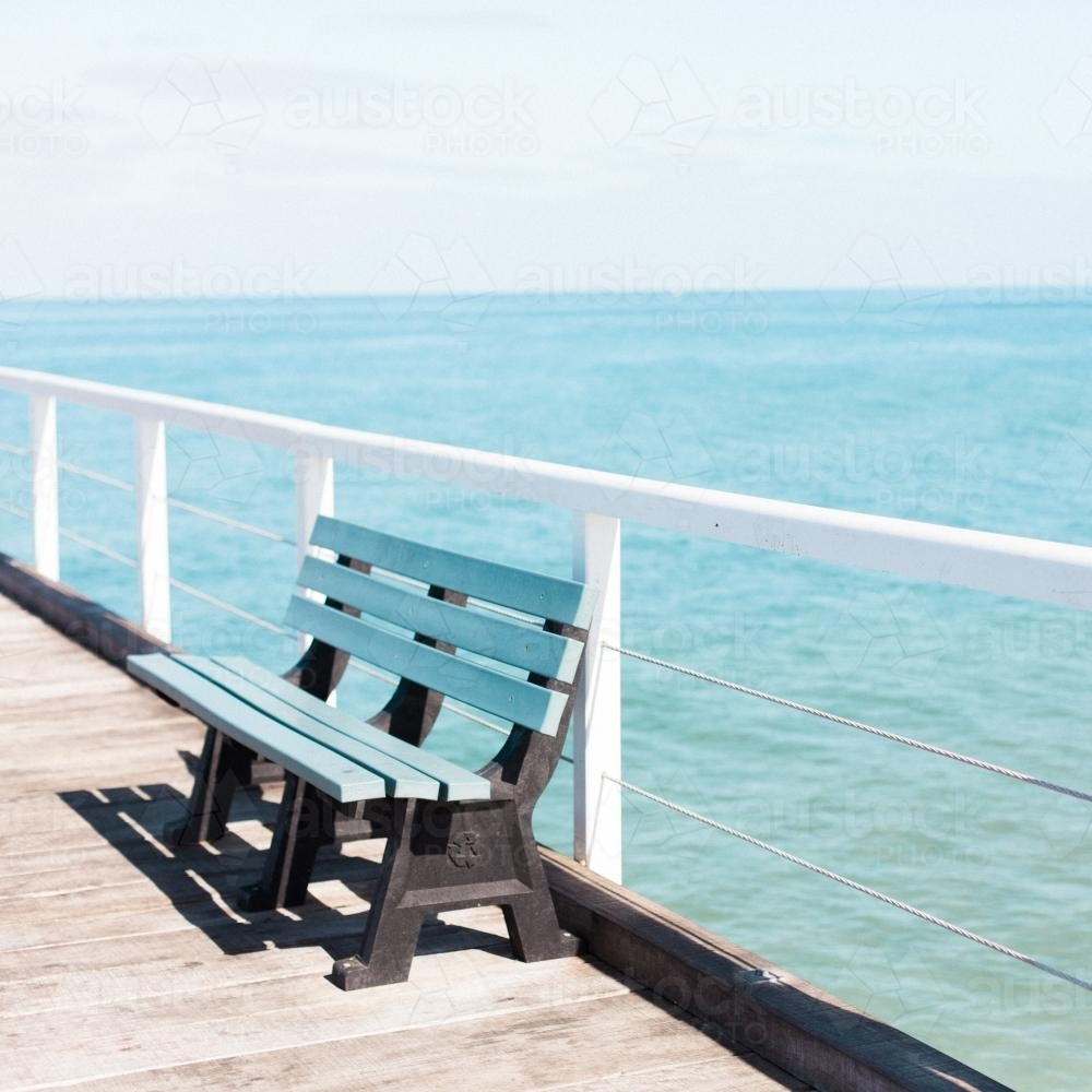 Park bench on a jetty overlooking ocean - Australian Stock Image