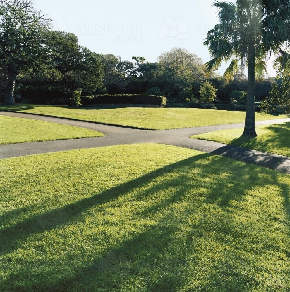Paved pathways through parkland with light and shadow - Australian Stock Image