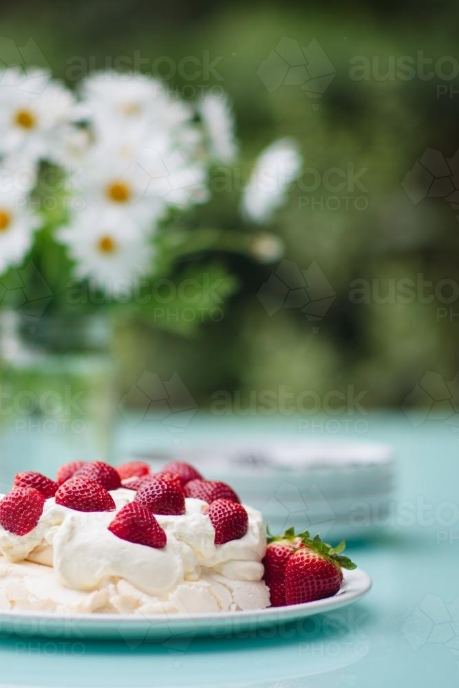 Pavlova topped with strawberries set out on a table outdoors in summer - Australian Stock Image