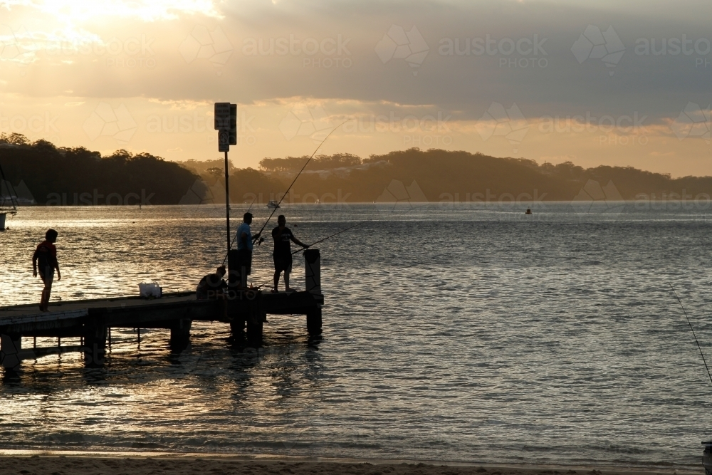 People fishing of a pier at dusk - Australian Stock Image