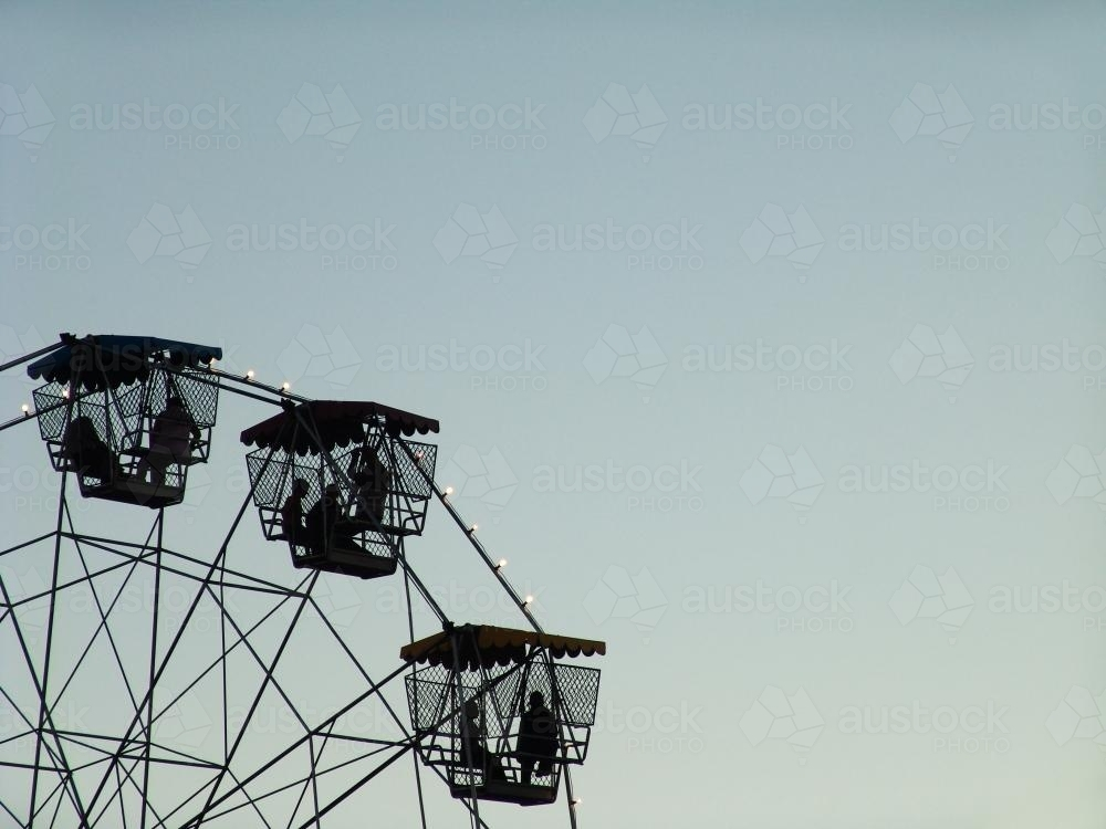 People in a ferris wheel silhouetted against a blue sky - Australian Stock Image