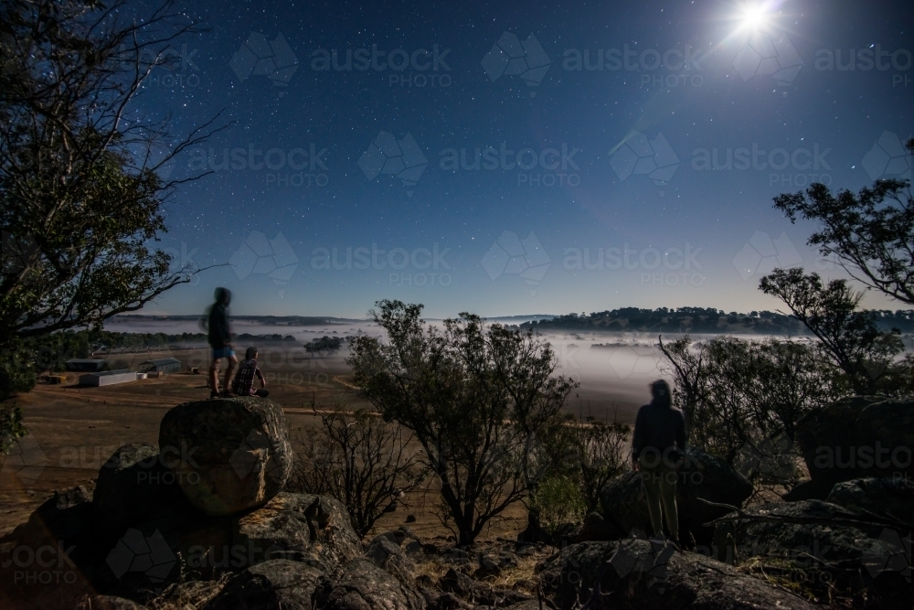 People looking out over paddock night time fog - Australian Stock Image