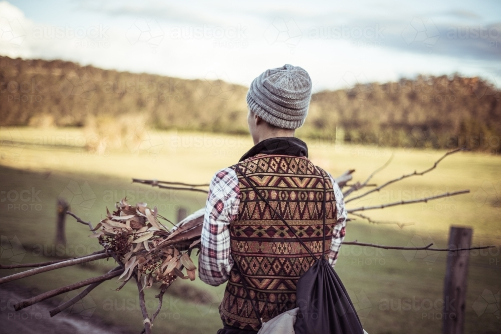 Person carrying sticks kindling for fire - Australian Stock Image