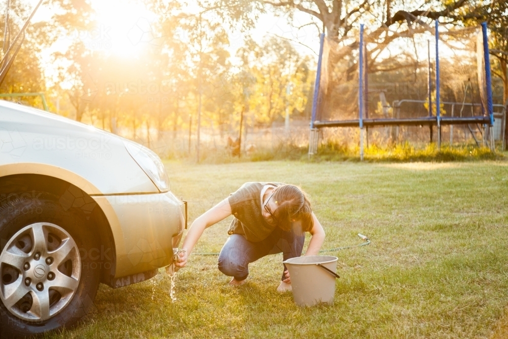Person hand washing front of family car in backyard in natural light flare - Australian Stock Image