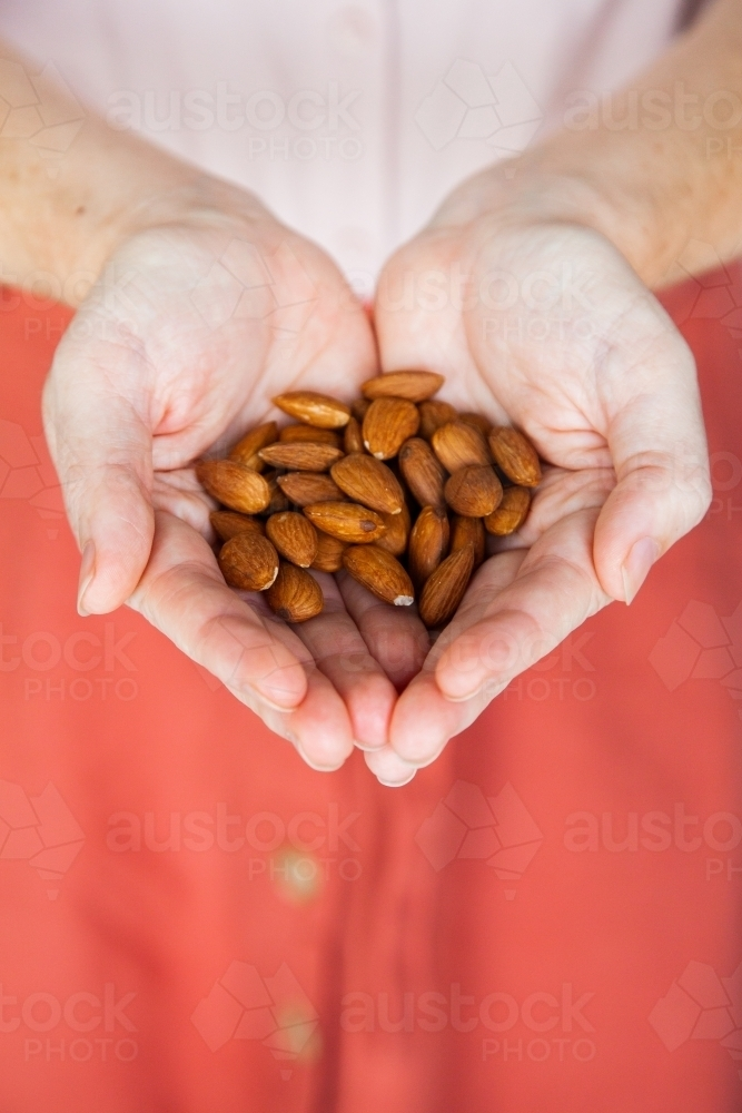 Person holding healthy snack of almond nuts in her hands - Australian Stock Image