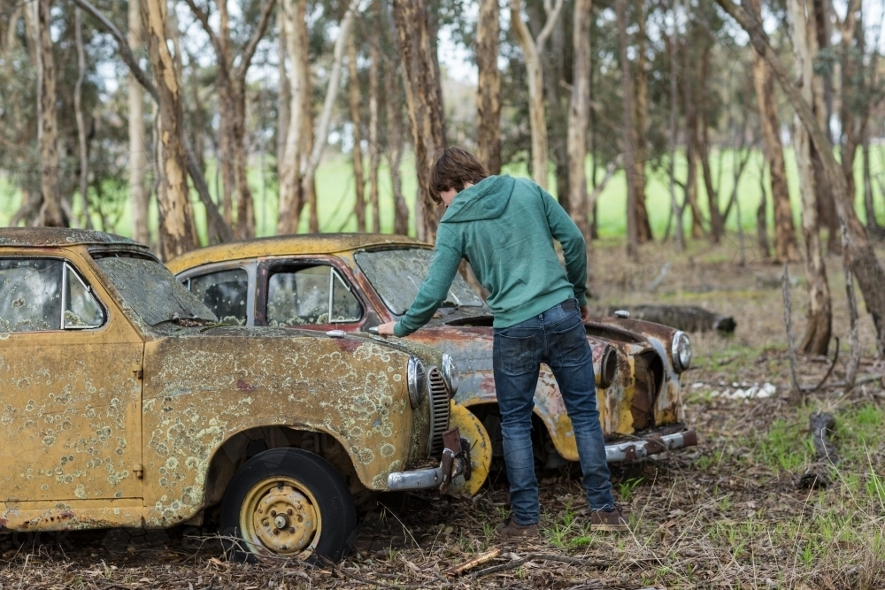 Image of Person looking at old junk cars - Austockphoto