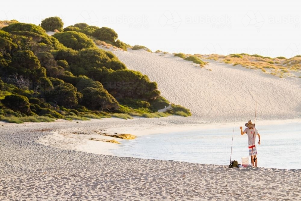 Person standing on the beach Fishing - Australian Stock Image