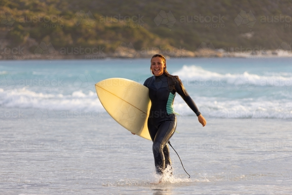 Person walking out of the water carrying surfboard on beach - Australian Stock Image