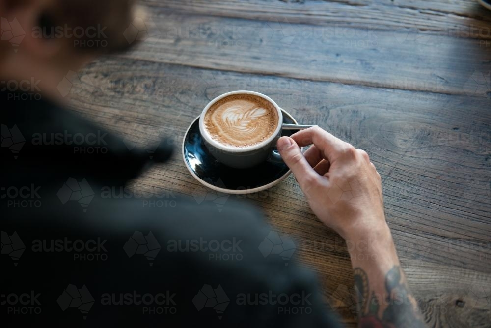 Person with a coffee on a wooden table - Australian Stock Image