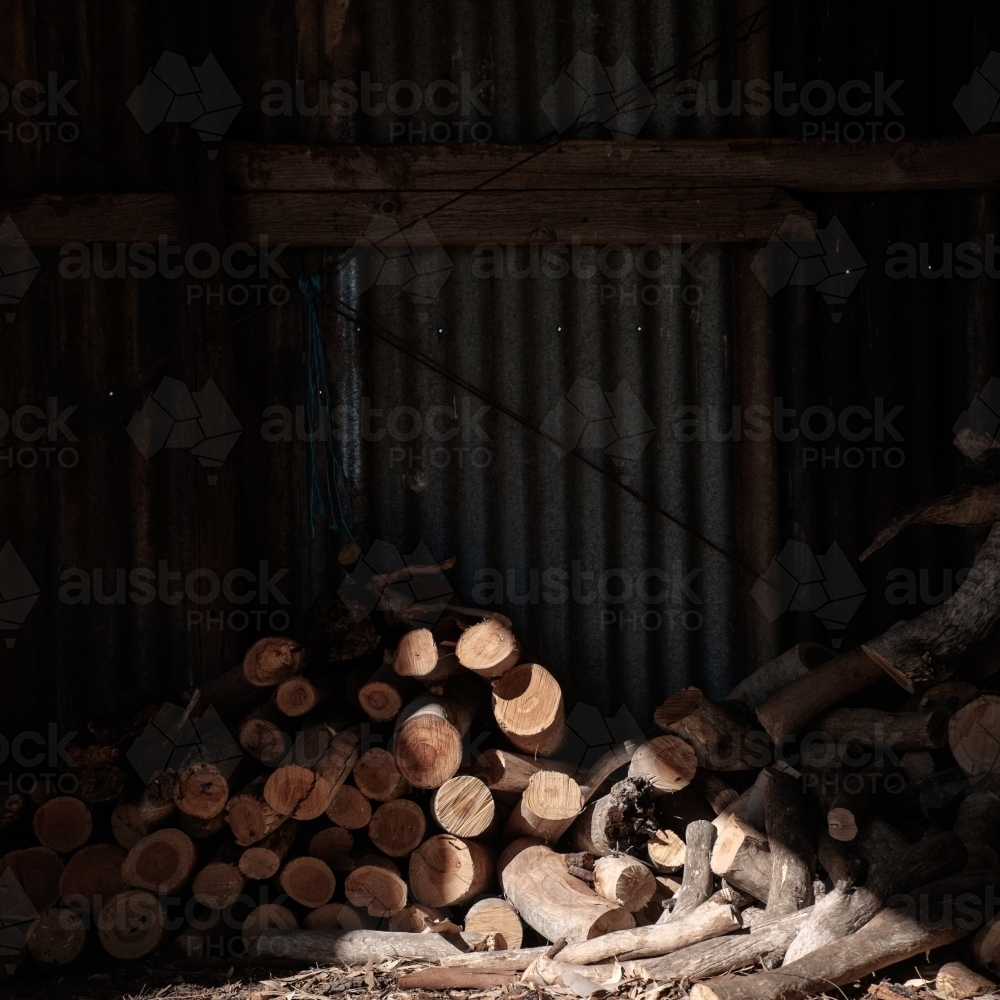 Pile of firewood in sunlit shed - Australian Stock Image