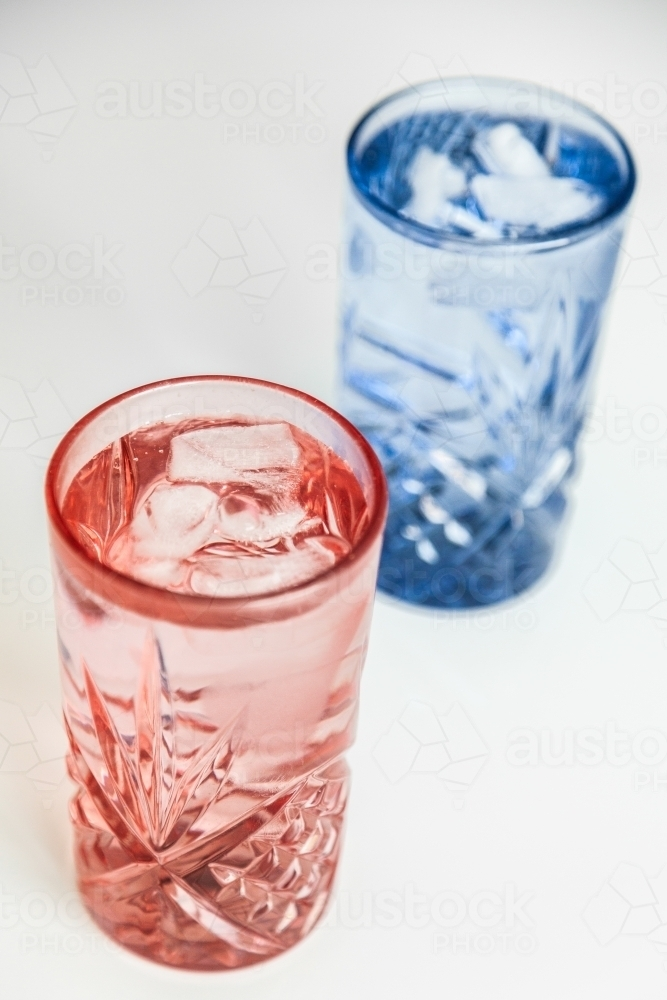 Pink and blue water glass with ice in it - cool refreshing healthy drink - Australian Stock Image