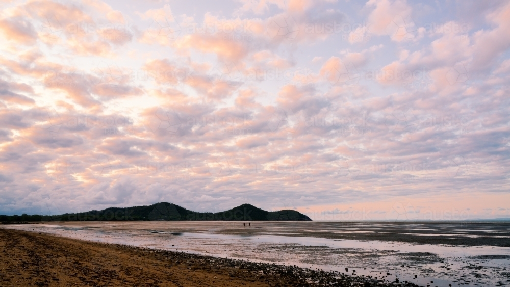 Pink clouds reflected in the tidal waters. - Australian Stock Image