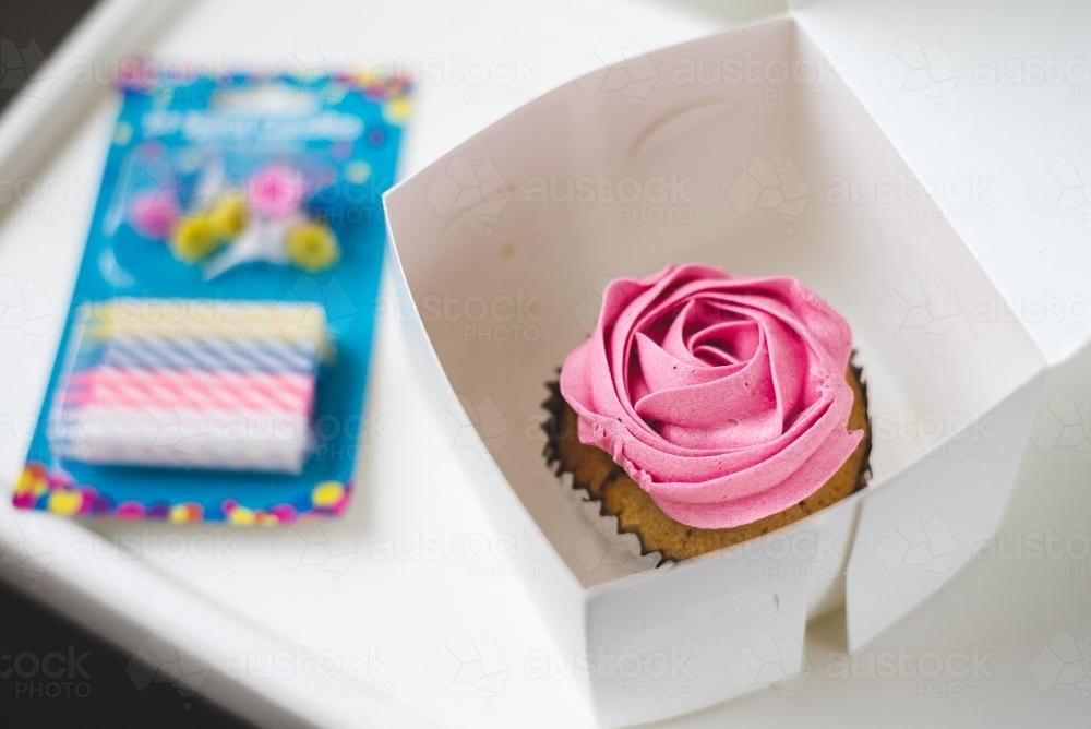 Pink cupcake and birthday candles - Australian Stock Image