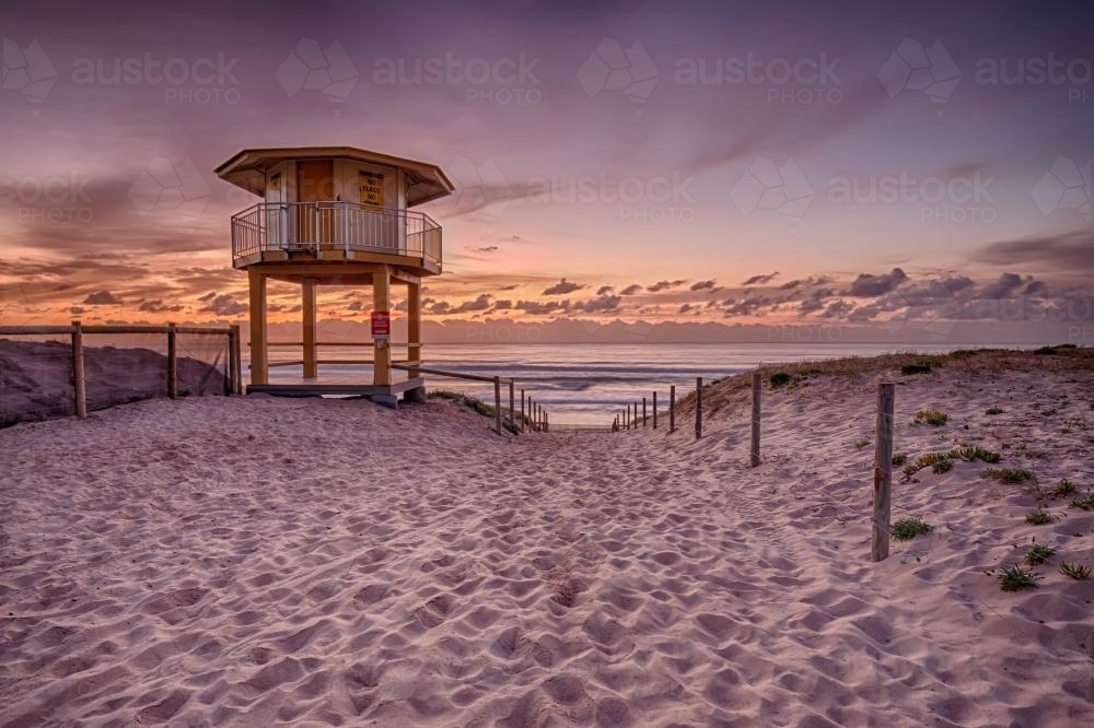 Pink Sunrise Over Ocean with Lifegaurd Tower in Foreground - Australian Stock Image