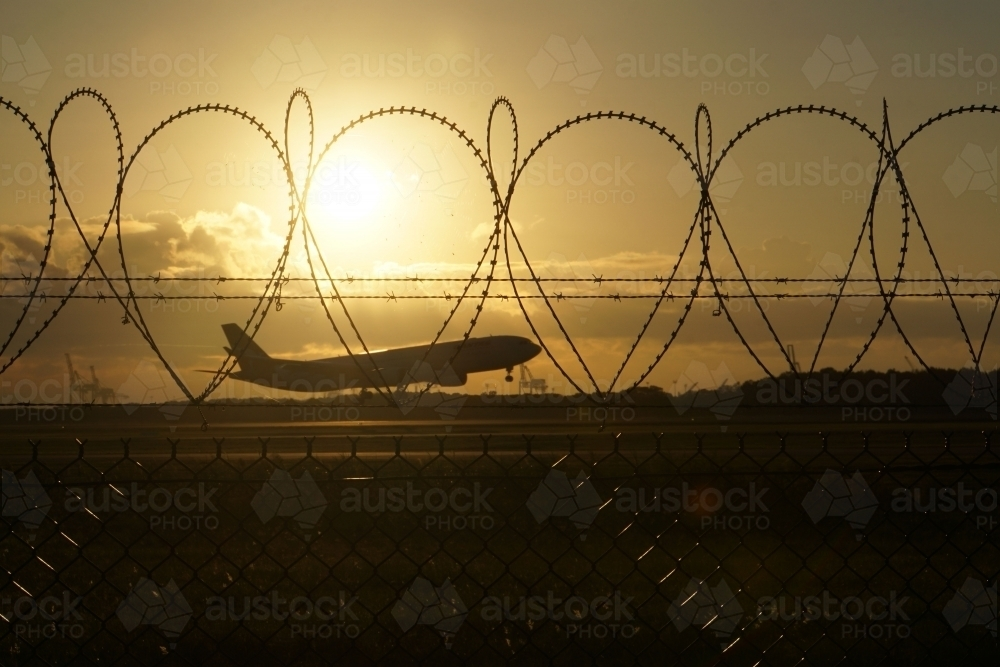 Plane landing at sunrise through security fence - Australian Stock Image