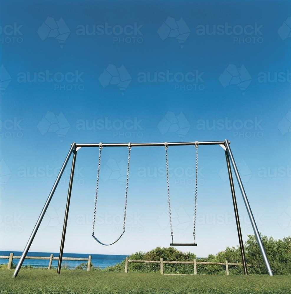 Playground swing set with blue sky and ocean background - Australian Stock Image
