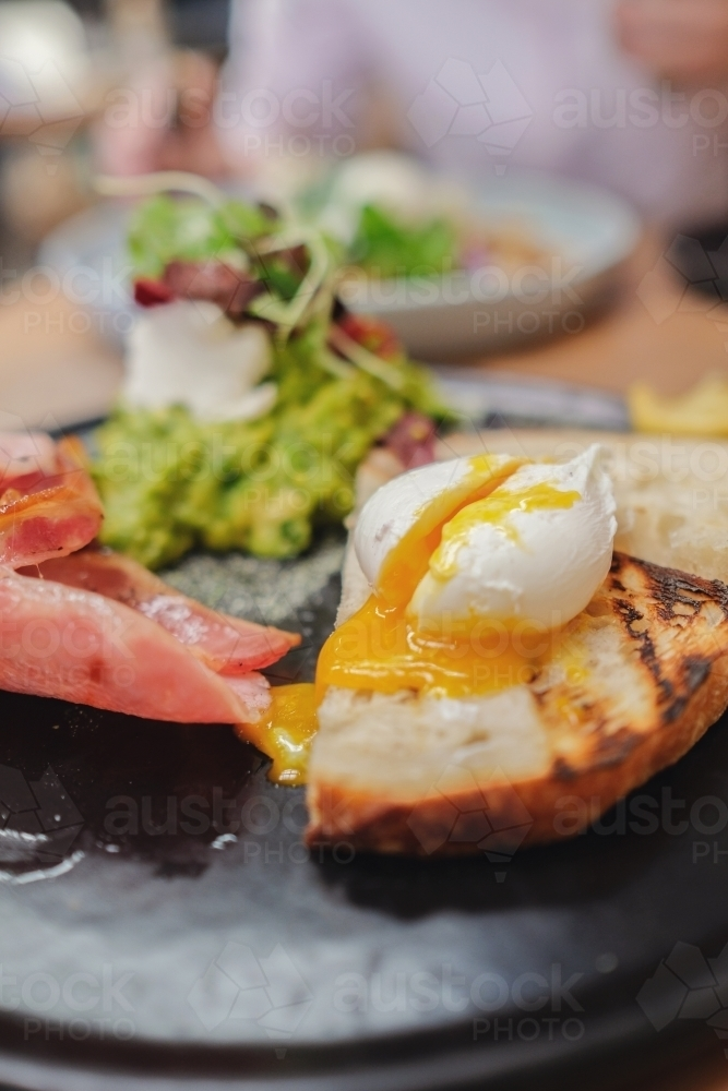 Poached egg on sourdough toast with bacon and mashed avocado - Australian Stock Image