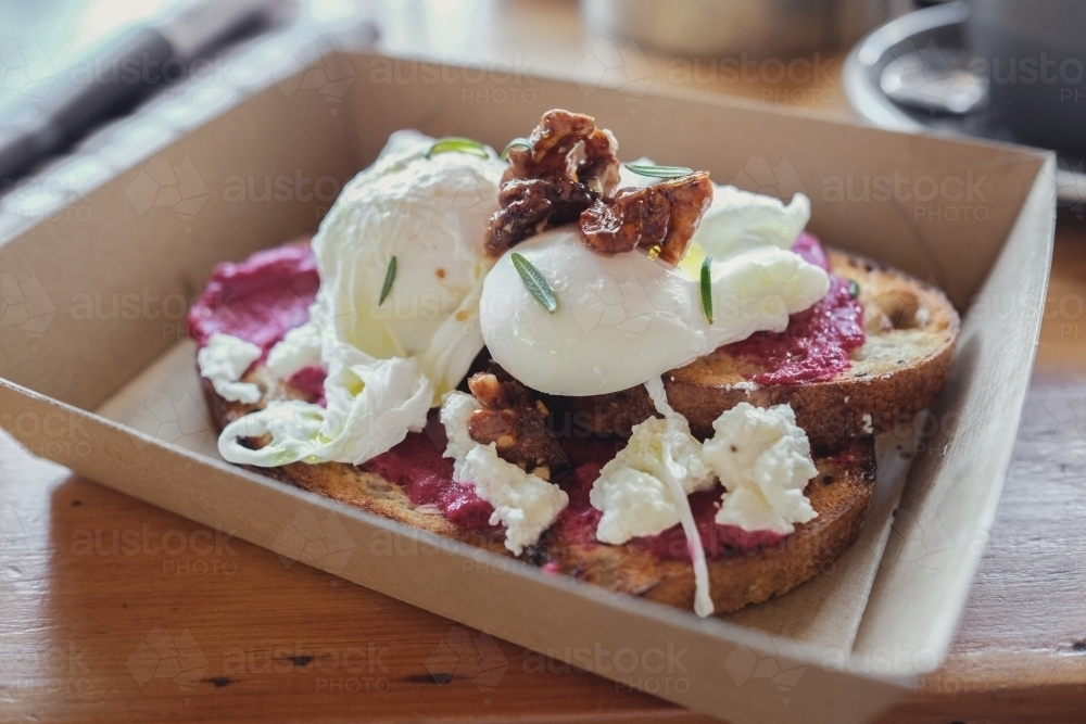 Poached eggs and beetroot puree on wood-fired sourdough toast - Australian Stock Image