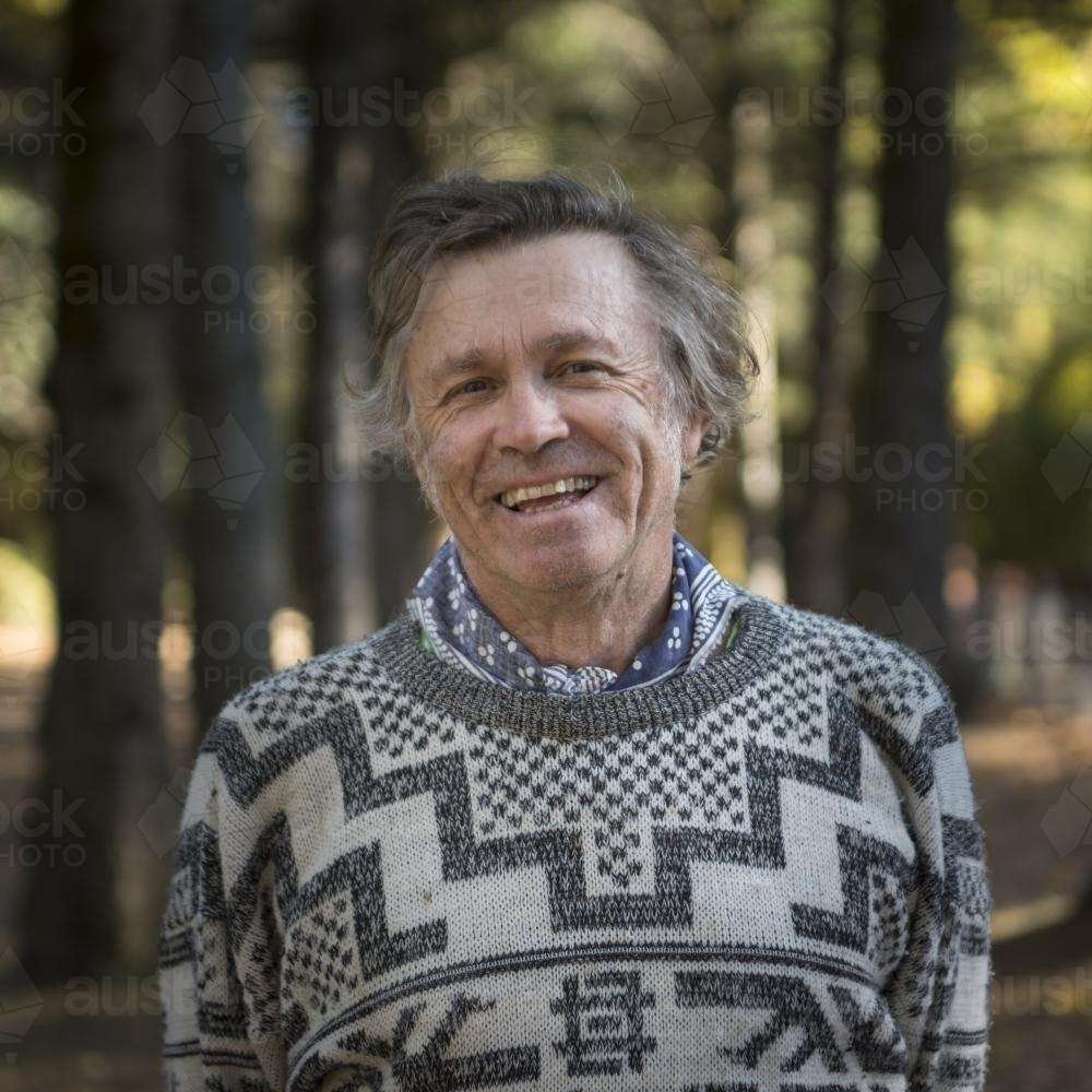 Portrait of a happy middle aged man among huge trees in the park - Australian Stock Image