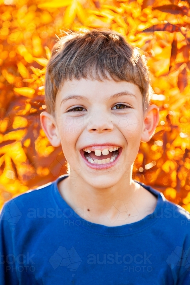 Portrait of a happy young boy laughing in autumn - Australian Stock Image