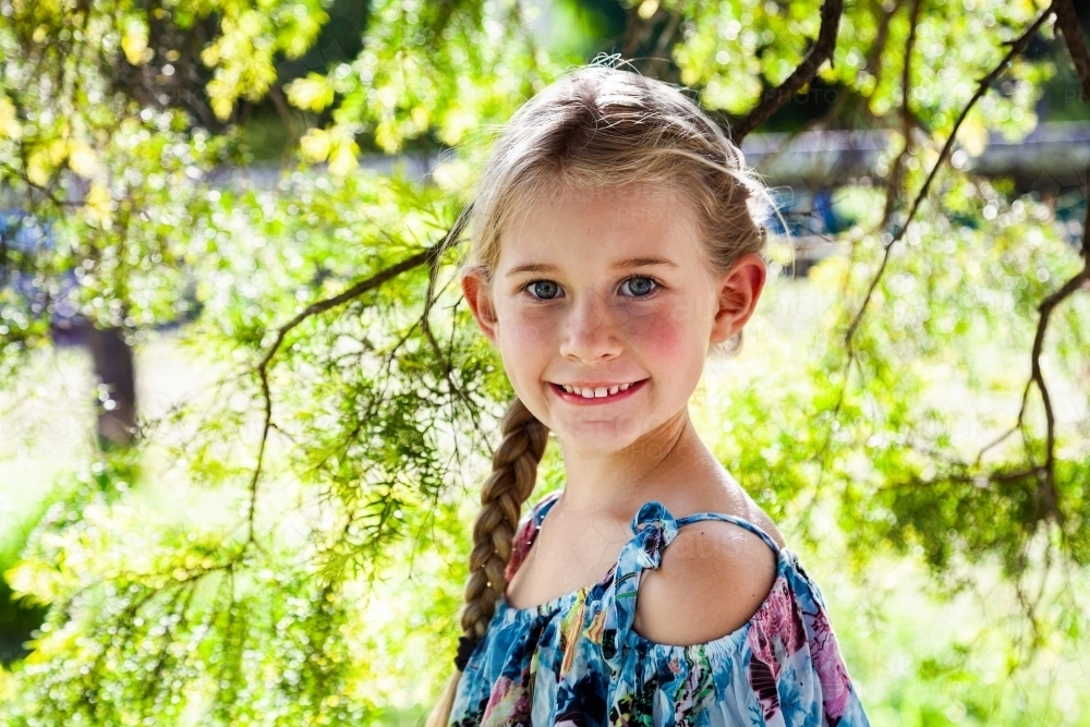 Portrait of a happy young girl with blonde hair outside - Australian Stock Image