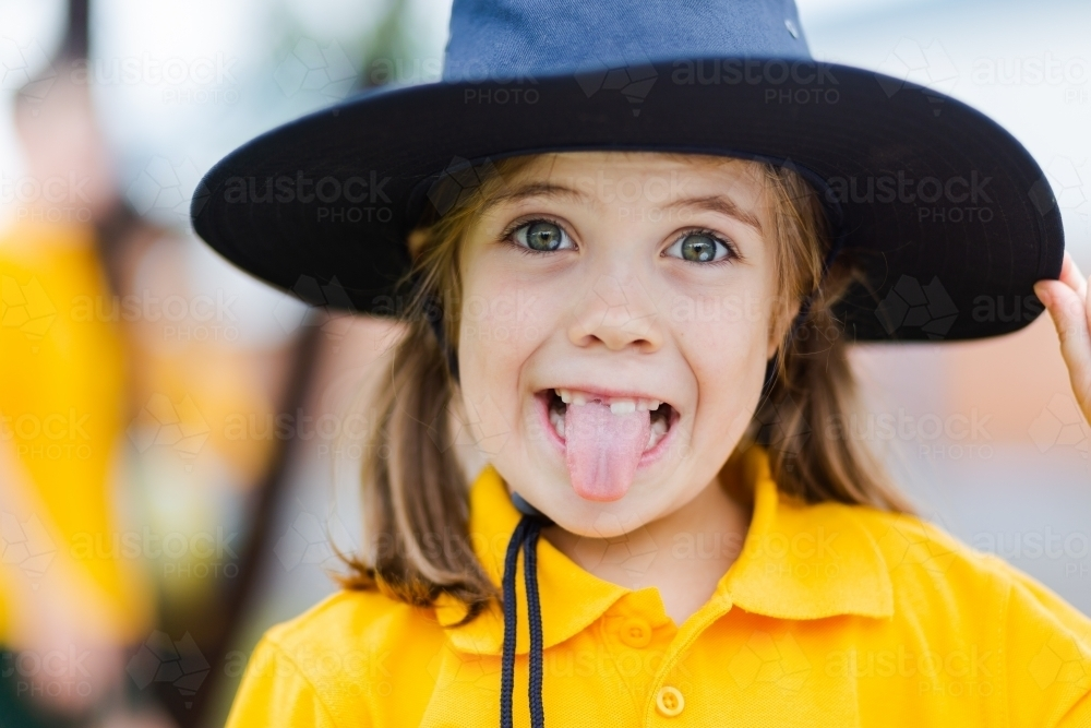 Portrait of a happy young school girl making a silly face outside wearing a hat for sun protection - Australian Stock Image