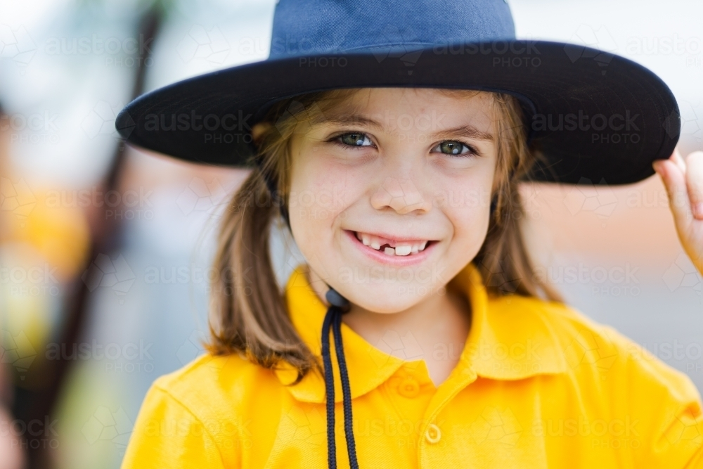 Portrait of a happy young school girl outside wearing a hat for sun protection - Australian Stock Image