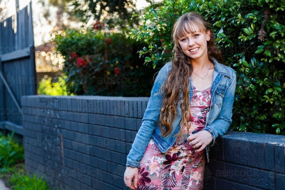 Portrait of a happy young woman leaning on a wall - Australian Stock Image
