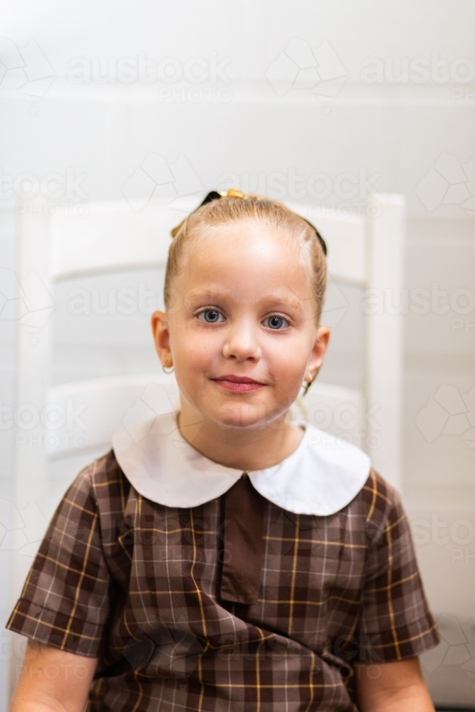 Portrait of a school girl in uniform sitting on chair at home before school - Australian Stock Image