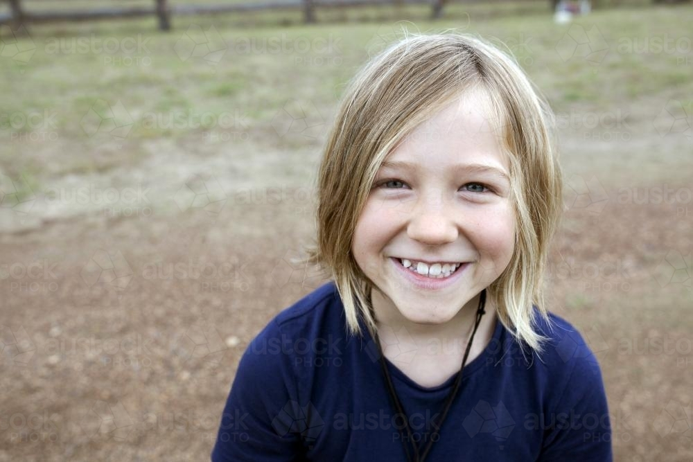 Portrait of a smiling blonde girl standing outside - Australian Stock Image