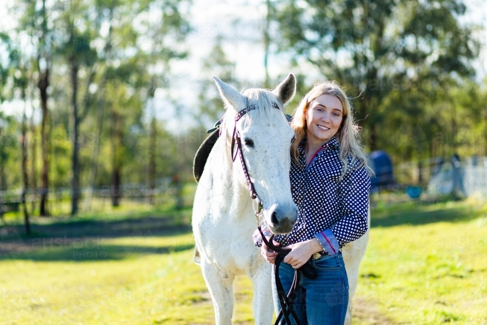 Portrait of a teen horserider in paddock with her horse and copy space - Australian Stock Image