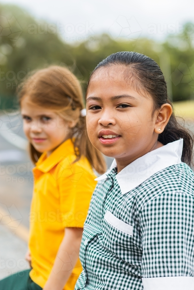 Portrait of a young Australian girl of Filipino ethnicity sitting outside school - Australian Stock Image