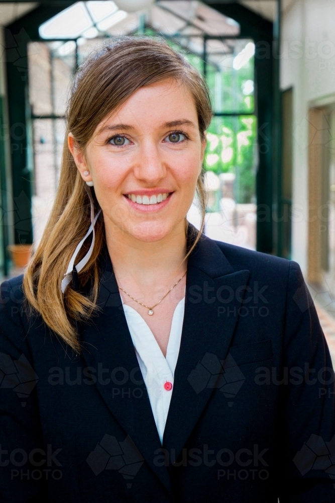 Portrait of a young female office worker standing near the exit of the building - Australian Stock Image