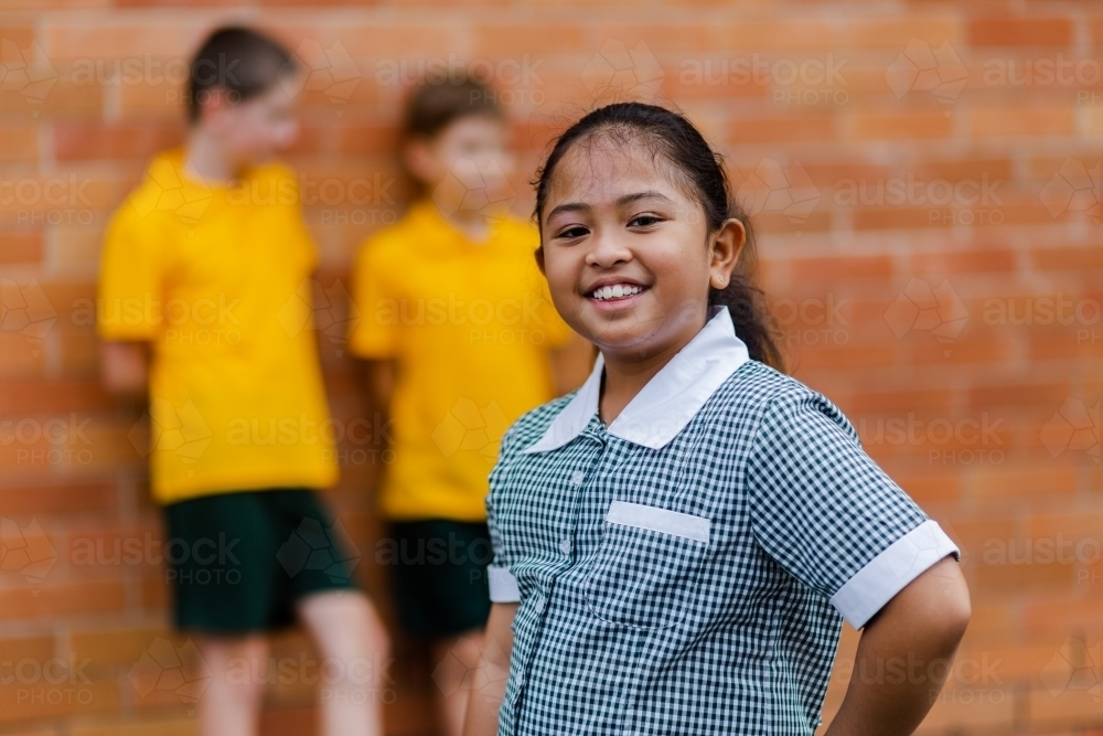 Portrait of happy young Aussie school girl of Filipino ethnicity smiling and wearing a dress - Australian Stock Image