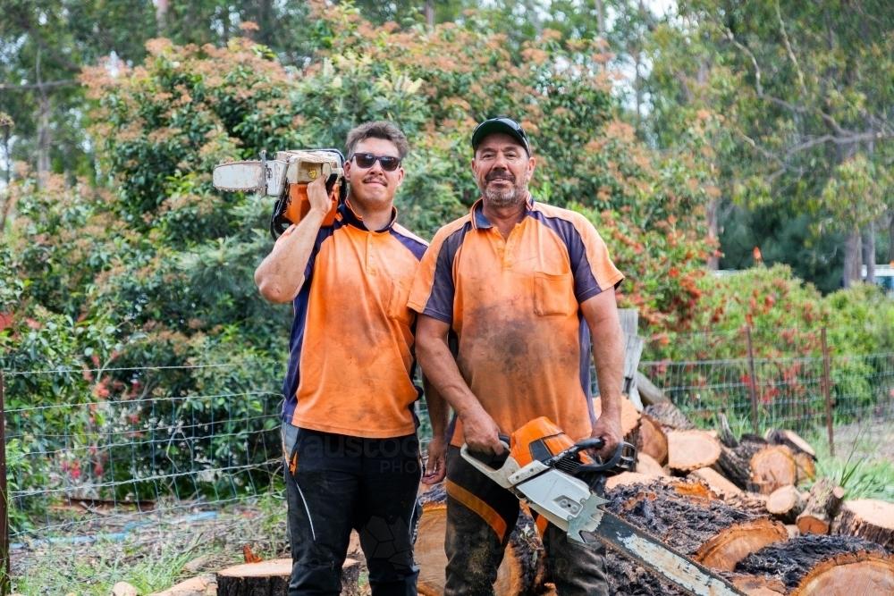 Portrait of two happy aussie blokes with chainsaws - lumberjack tree felling services - Australian Stock Image